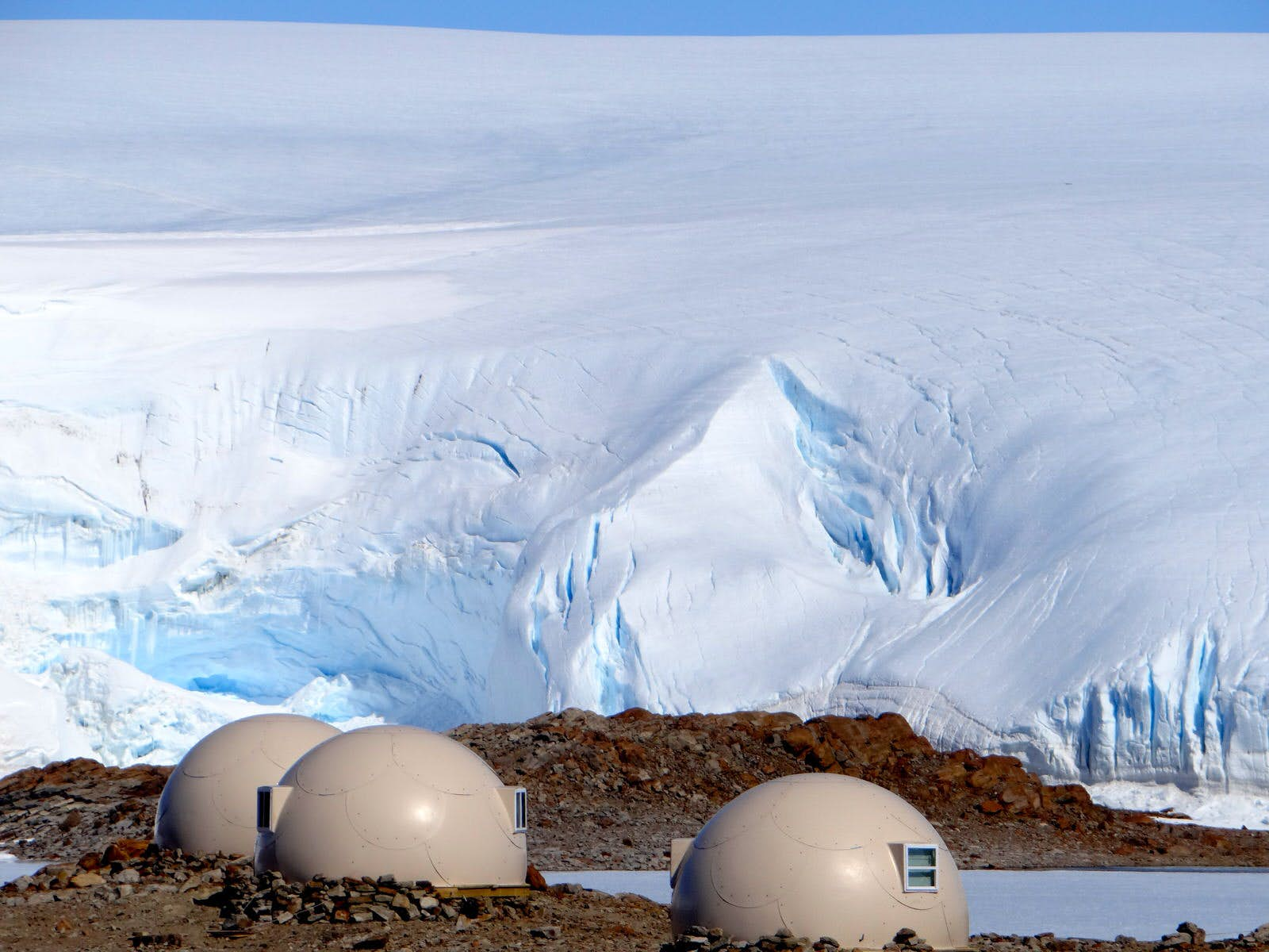 Cream-coloured domes stand in the Antarctica, with huge icebergs in the background.