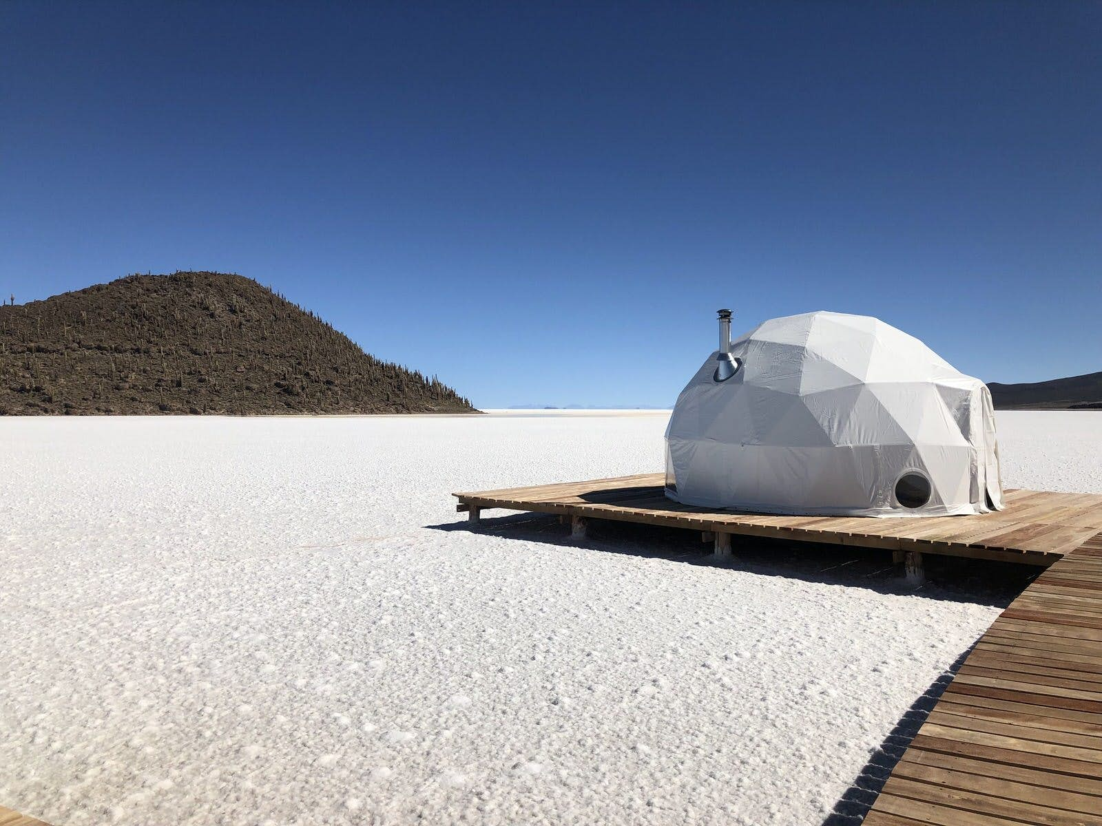 A white geodesic domed tent with a silver chimney sits on a raised wooden platform, which seemingly hovers over white salt flats; in the semi-distance is a forested hill rising from the flats, much like an island